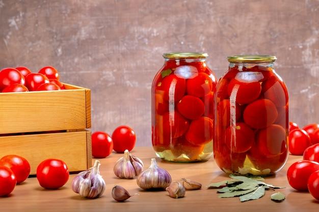 Tomates fraîches et en conserve. composition avec des tomates marinées dans des bocaux en verre.