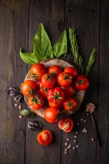 Tomates fraîches dans une assiette sur fond sombre récolte de tomates