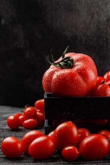 Tomates fraîches dans une boîte en bois sur un mur gris et foncé, vue latérale.