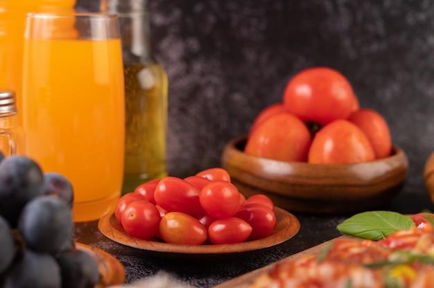 Tomates fraîches dans une tasse en bois, raisins et jus d'orange dans un verre.
