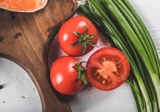Tomates fraîches entières et demi coupées aux herbes vertes