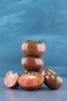 Tomates fraîches entières et tranchées bio sur marbre.