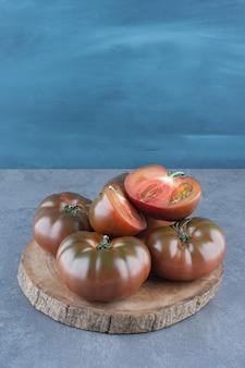 Tomates fraîches entières et tranchées biologiques sur morceau de bois.