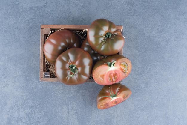 Tomates fraîches entières et tranchées dans une boîte en bois.