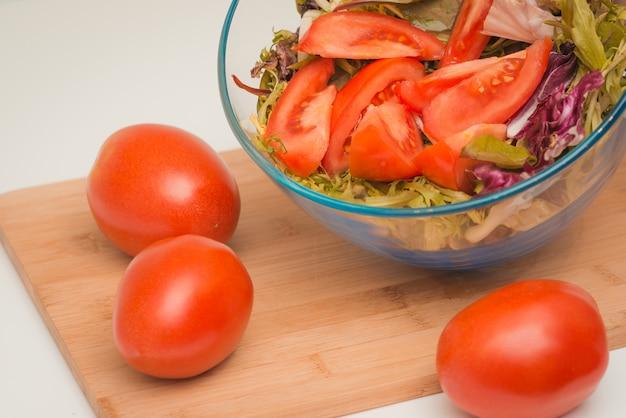 Tomates fraîches, juteuses et charnues et bol avec salade sur une planche à découper, sur un tableau blanc.