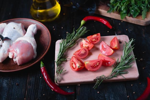 Tomates fraîches juteuses sur une planche à découper, cuisses de poulet et épices sur la table