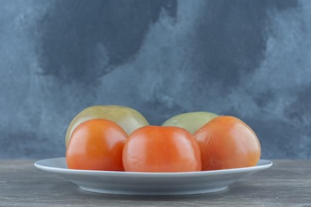 Tomates fraîches marinées et rouges sur une plaque blanche sur une table grise.