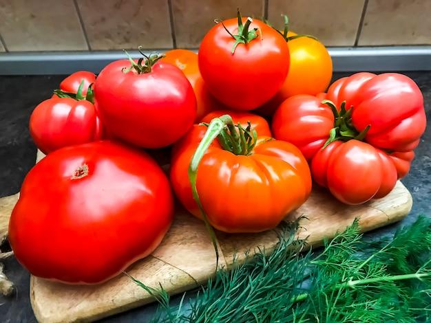 Tomates fraîches multicolores sur planche de cuisine en bois.
