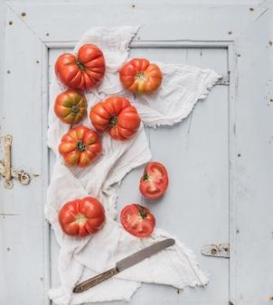 Tomates fraîches mûres dans un plateau en bois bleu rustique