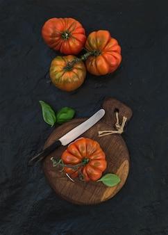 Tomates fraîches mûres et feuilles de basilic sur une planche en bois rustique