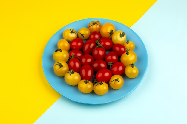 Tomates fraîches mûres rouges et jaunes à l'intérieur de la plaque bleue sur le bureau bleu glacier et jaune