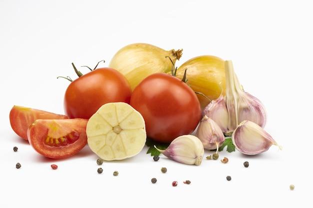 Tomates fraîches, oignons et ail, mélange de poivre isolé sur fond blanc.