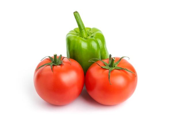 Tomates fraîches et poivrons biologiques sur fond blanc.