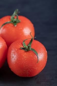 Tomates fraîches rouges sur une surface sombre.