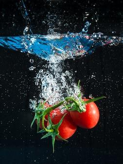 Tomates fraîches tombant dans l'eau