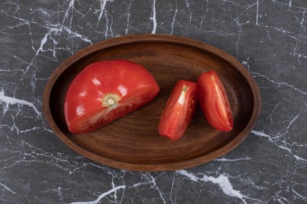 Tomates fraîches en tranches sur une plaque en bois.