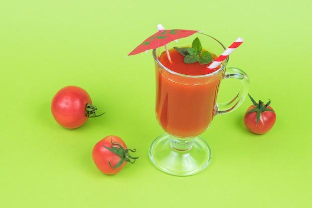 Tomates fraîches et un verre en verre avec du jus de tomate sur fond vert.