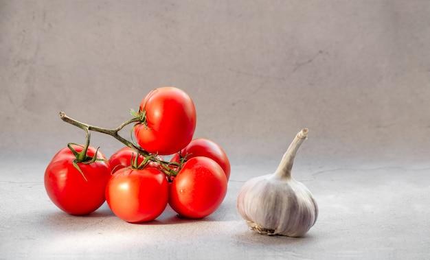 Tomates fraîches sur une vigne à l'ail sur fond clair.