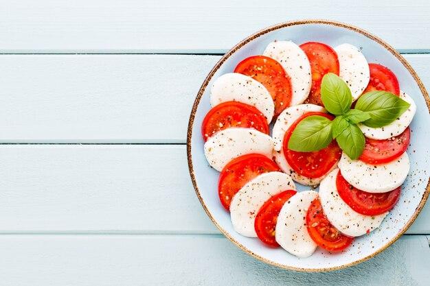 Tomates, fromage mozzarella, basilic et épices sur tableau en ardoise grise. ingrédients de la salade caprese traditionnelle italienne. un plat méditerranéen.