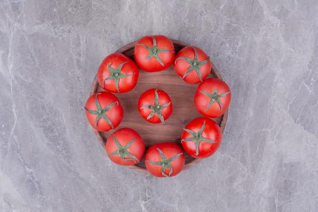 Tomates isolées dans un plateau en bois sur le marbre