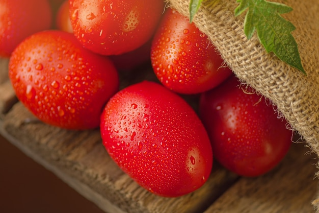 Tomates italiennes longues sur table en bois. tas de tomates fraîches dans un sac de jute sur table en bois. concept de produit naturel.