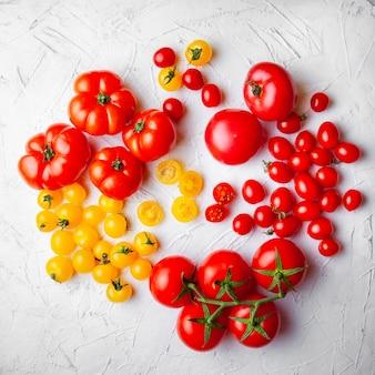 Tomates jaunes et rouges sur fond texturé blanc. vue de dessus.