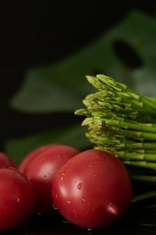 Tomates lavées et asperges en gouttes d'eau se trouvent sur un fond sombre vertical close up