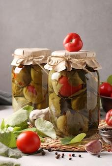 Tomates marinées à l'ail en feuilles de vigne dans deux bocaux en verre sur surface grise
