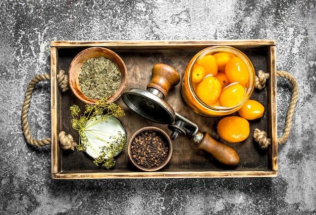 Tomates marinées aux épices, herbes et seamer sur plateau en bois sur table rustique.