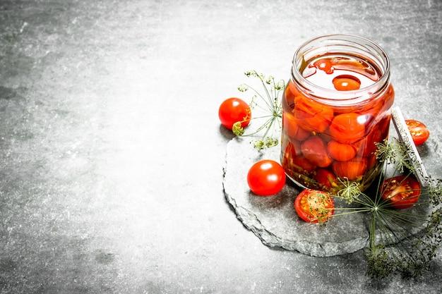 Tomates marinées aux herbes. sur un fond de pierre.