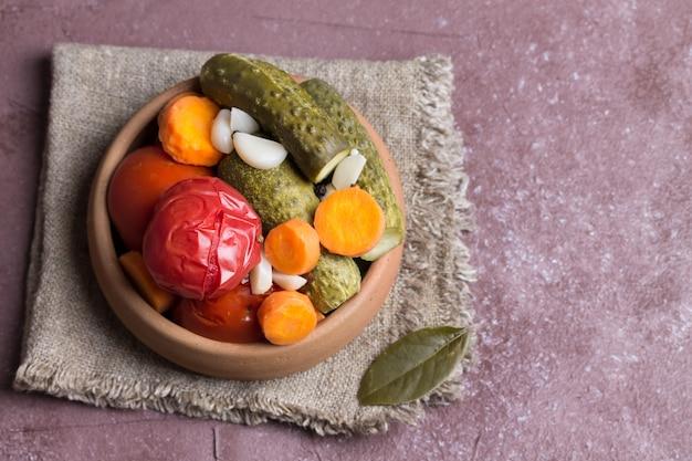 Tomates marinées et concombres en poterie