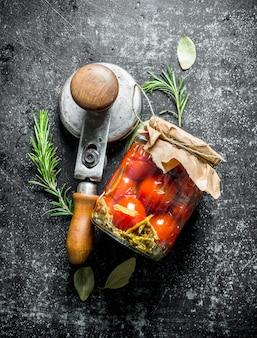 Tomates marinées dans un bocal en verre avec du romarin. sur fond rustique foncé