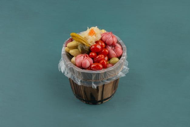 Tomates marinées, olives, ail, chou, concombres dans un seau en bois.