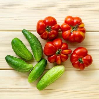 Tomates mûres et concombres sur un fond en bois clair, vue du dessus.