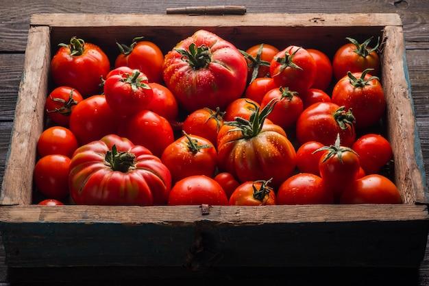 Tomates mûres dans une boîte en bois légumes frais sur fond de bois noir