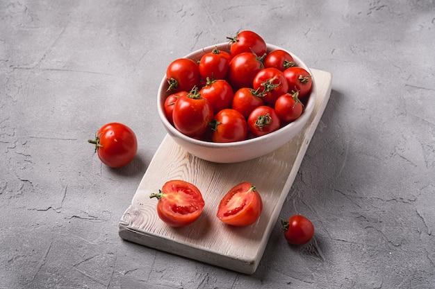 Tomates mûres fraîches entières et tranchées dans un bol et sur une vieille planche à découper en bois, table en béton en pierre, vue d'angle