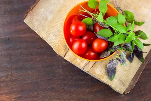 Tomates mûres fraîches, feuilles de basilic vert et violet dans un bol sur une planche à découper en bois