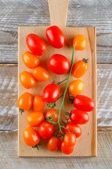 Tomates mûres sur planche de bois et à découper. pose à plat.
