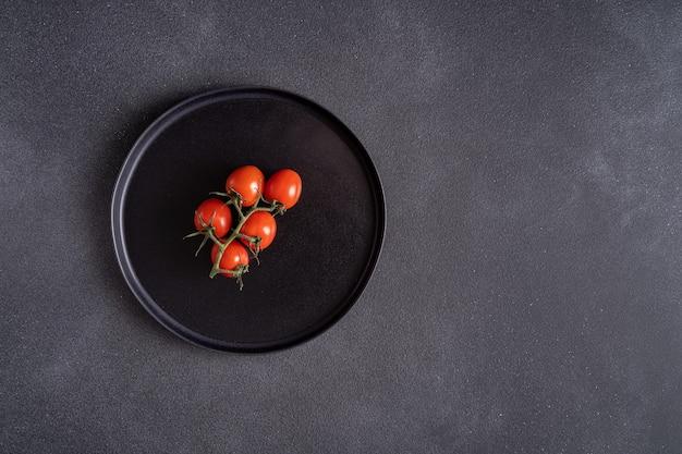 Tomates mûres rouges sur plaque noire