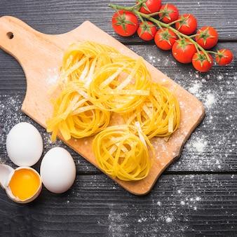 Tomates mûres; tagliatelles crues avec oeufs cassés et entiers sur planche de bois