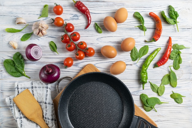 Tomates, oeufs, oignons, épinards et poivrons biologiques frais sur une table en bois avec une poêle à frire
