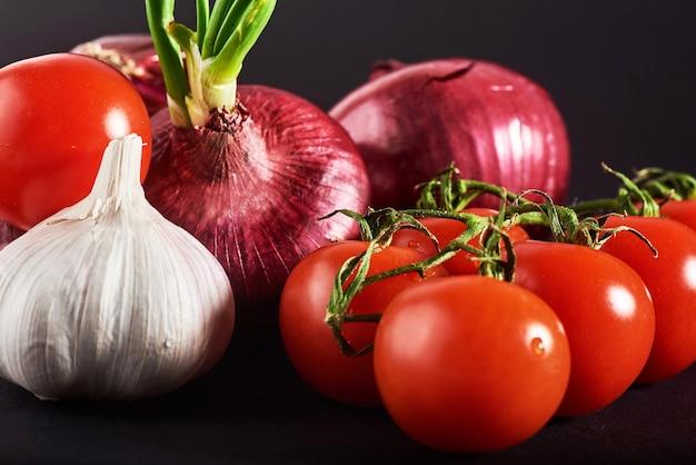 Les tomates, les oignons et l'ail sont isolés sur un fond noir