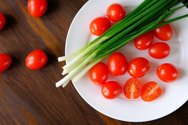 Tomates et oignons verts sur une assiette. légumes du jardin. produits agricoles biologiques naturels, végétarisme, végétalisme, aliments crus. mise en conserve pour l'hiver, récolte. la vie à la maison.