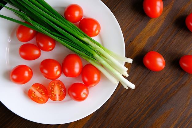 Tomates et oignons verts sur une assiette