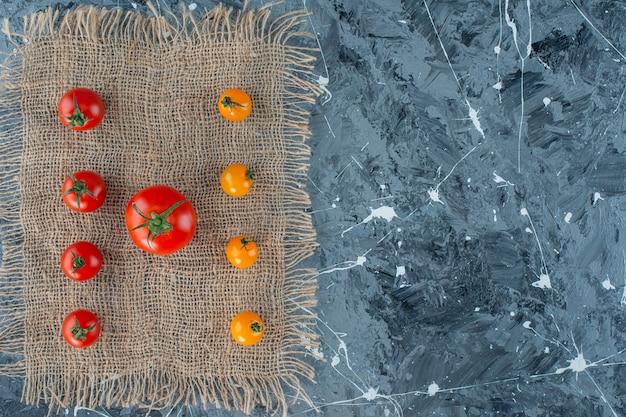 Tomates orange et tomates rouges sur une serviette en toile de jute sur la surface en marbre