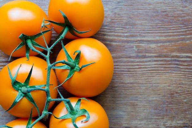 Tomates oranges juteuses fraîches sur table en bois vintage