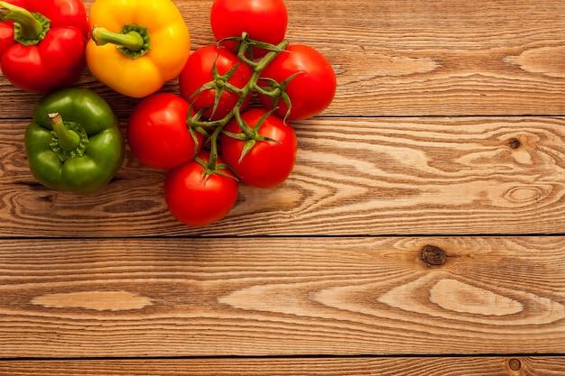 Tomates et poivrons sur fond de bois