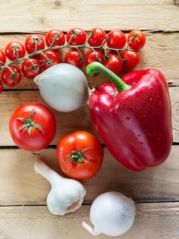 Tomates, poivrons, oignons et ail sur une surface en bois