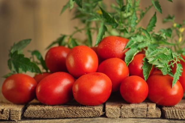 Tomates roma juteuses biologiques fraîches. tomates roma sur table en bois