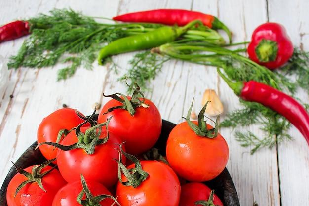 Tomates rouges biologiques fraîches dans une plaque noire sur une table en bois blanche avec des poivrons verts et rouges et rouges, des poivrons verts, des grains de poivre noirs, sel, gros plan, concept santé